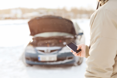transportation, winter and vehicle concept - closeup of man with broken car and smartphone photo