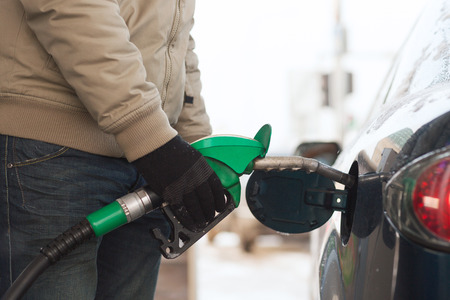 benzine: vehicle and fuel concept - close up of male refilling car fuel tank