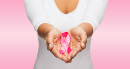 breasts: healthcare and medicine concept - womans hands holding pink breast cancer awareness ribbon