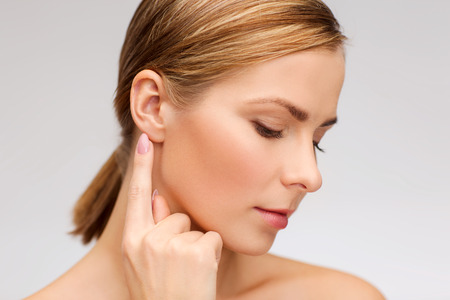 ear: health and beauty concept - face of beautiful woman touching her ear Stock Photo