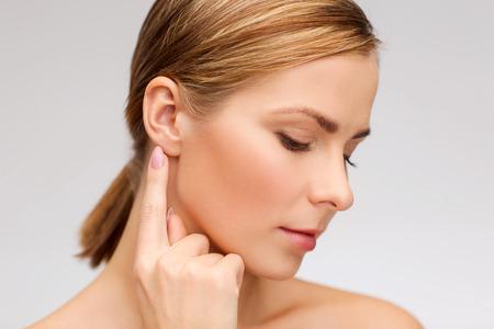 escuchar: la salud y el concepto de belleza - cara de hermosa mujer tocando su oreja
