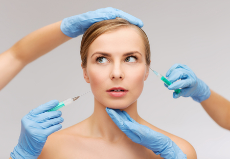 beauty surgery: healthcare, beauty and medicine concept - beautiful scared woman face with closed eyes and beautician hands with syringe