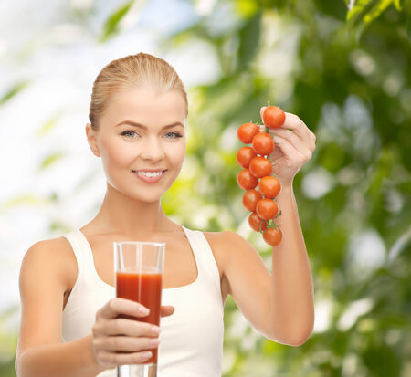 gitness and diet concept - young woman holding glass of juice and tomatoes photo