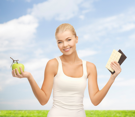 fitness and diet concept - sporty woman with apple and chocolate bars photo