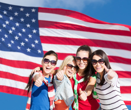 citizenship: summer, holidays, vacation, happy people concept - beautiful teenage girls or young women showing thumbs up