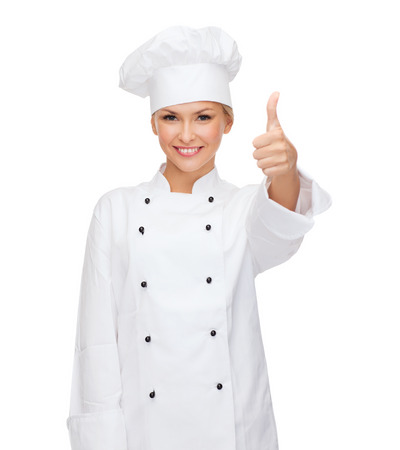 cooking, gesture and food concept - smiling female chef, cook or baker showing thumbs up photo
