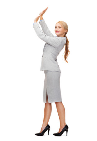 business and education concept - friendly young smiling businesswoman pushing up something imaginary photo