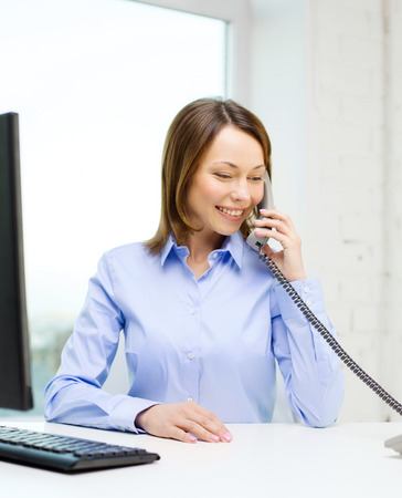 business, communication and education concept - smiling businesswoman with laptop and telephone photo