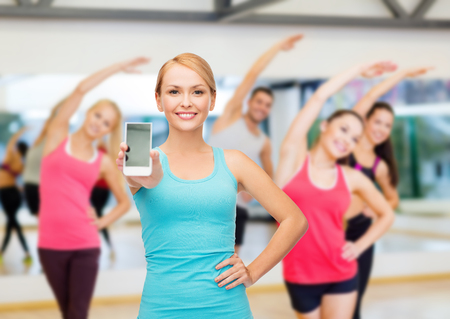 sport, excercise, technology, internet and healthcare - sporty woman with blank smartphone screen photo