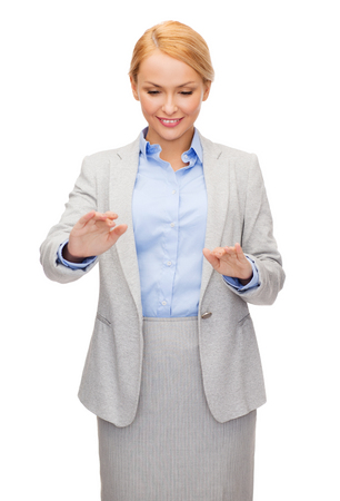 business and future technology concept - smiling businesswoman pointing to something or pressing imaginary button photo