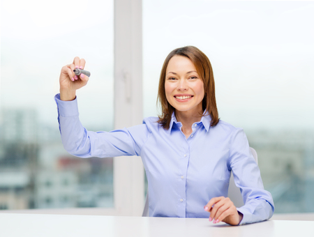 office, business, technology concept - businesswoman writing something in the air with marker Stock Photo - 25699070