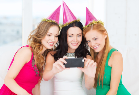 celebration, friends, bachelorette party, birthday concept - three smiling women in pink hats having fun with smartphone photo camera photo