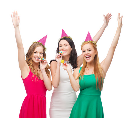 bachelorette party: celebration, friends, bachelorette party, birthday concept - three smiling women wearing pink hats and blowing favor horns and waving hands