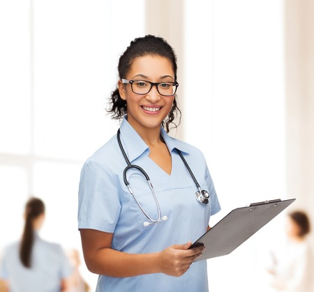healthcare and medicine concept - smiling female african american doctor or nurse in eyeglasses with stethoscope and clipboard photo