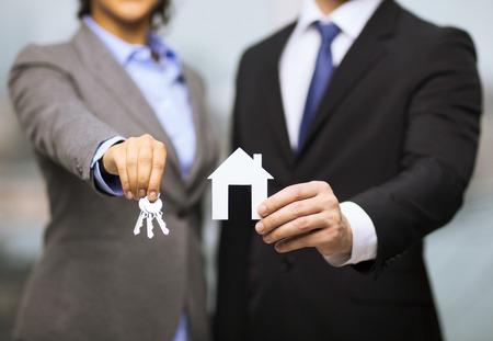 zakelijk: zakelijk, eco, vastgoed en kantoor concept - zakenman en zakenvrouw met wit papier huis en sleutels in het kantoor