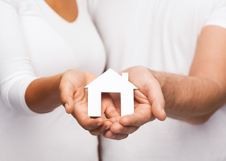 real estate and family concept - closeup of couple hands holding paper house photo