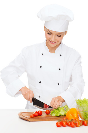 cooking and food concept - smiling female chef, cook or baker chopping vegetables
