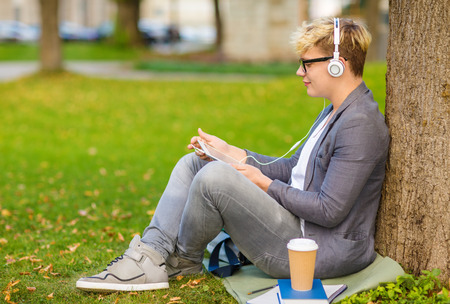 summer holidays, teenage, internet and technology concept - teenager with headphones, books, files, notebooks, coffee and tablet pc outside photo