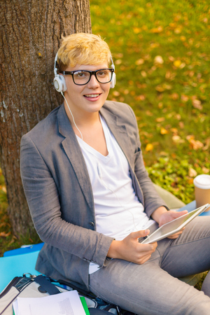 education, technology and internet concept - smiling male student in eyeglasses with tablet pc and headphones outdoors photo