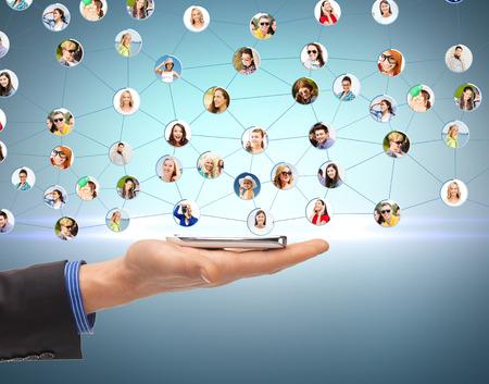 ビジネス、ネットワー キングおよびコミュニケーション - スマート フォンやソーシャル ネットワークと人間の手のクローズ アップ