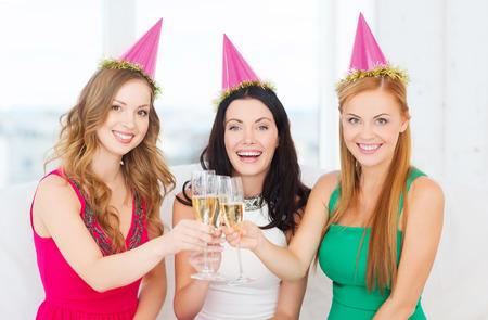 despedida de soltera: celebración, bebidas, amigos, despedida de soltera, cumpleaños concepto - tres mujeres sonrientes con sombreros de color rosa con una copa de champagne Foto de archivo