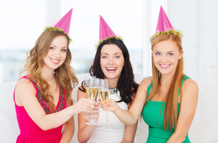 bachelorette party: celebration, drinks, friends, bachelorette party, birthday concept - three smiling women wearing pink hats with champagne glasses