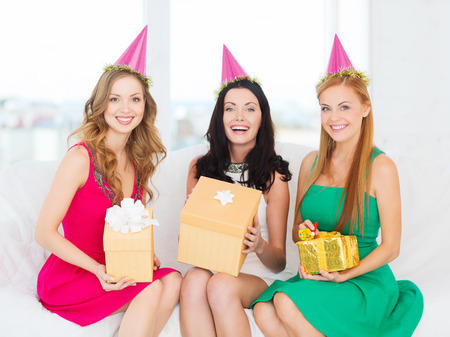 three gift boxes: celebration, friends, bachelorette party, birthday concept - three smiling women wearing pink hats with gift boxes