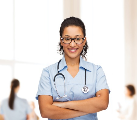 healthcare and medicine concept - smiling female african american doctor or nurse in eyeglasses with stethoscope photo