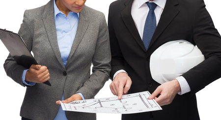 business, architecture and development concept - businesswoman and businessman with clipboard and white helmet pointing finger to blueprint photo