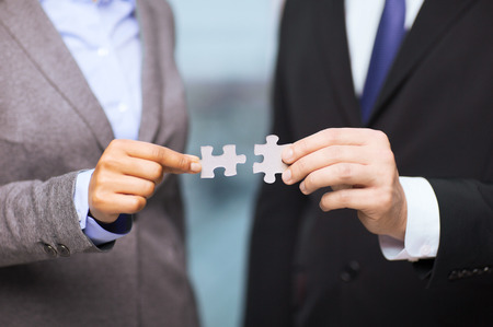 matching: business and office concept - businessman and businesswoman trying to connect puzzle pieces in office Stock Photo