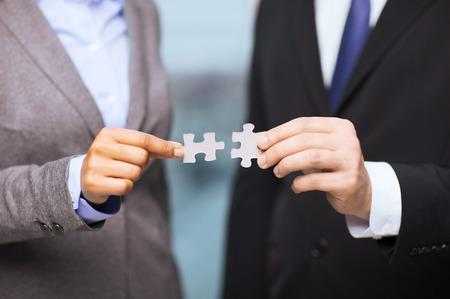 business en office concept - zakenman en zakenvrouw proberen om puzzelstukjes te verbinden in het kantoor