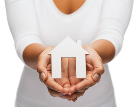hands holding house: real estate concept - closeup of woman hands holding paper house
