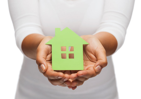 hands holding house: real estate and eco concept - closeup picture of woman hands holding green house