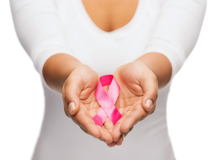 cancer ribbon: healthcare and medicine concept - womans hands holding pink breast cancer awareness ribbon