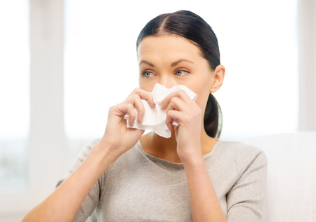 healthcare, medicine and home concept - sick girl with paper tissue photo