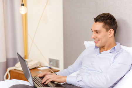 business, technology, internet and hotel concept - happy businessman with laptop computer lying in hotel in bed photo