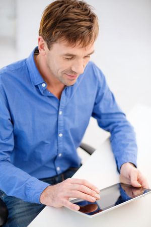 technology and lifestyle, distance learning concept - handsome man working with tablet pc at home photo