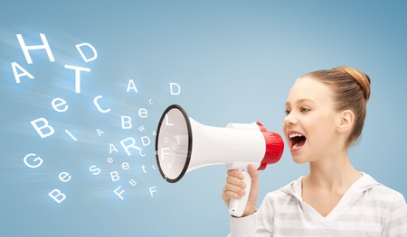 communication concept - girl with megaphone over blue background photo