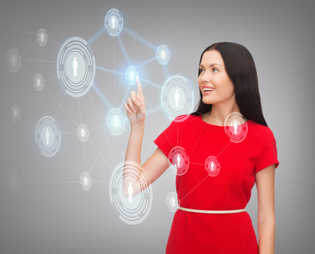 business, communication and future technology concept - attractive young woman in red dress pointing her finger at business network photo