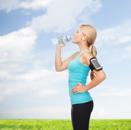 sport, excercise, technology, internet and healthcare - sporty woman listening to music from smartphone with water bottle photo