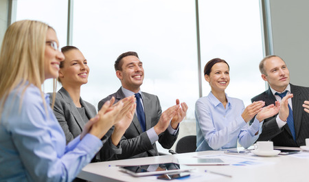 congratulating: business, technology and office concept - happy business team with laptop computers, documents and coffee clapping hand