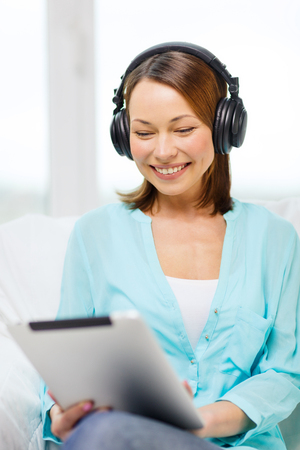 home, technology and internet concept - smiling woman sitting on the couch with tablet pc conputer and headphones at home