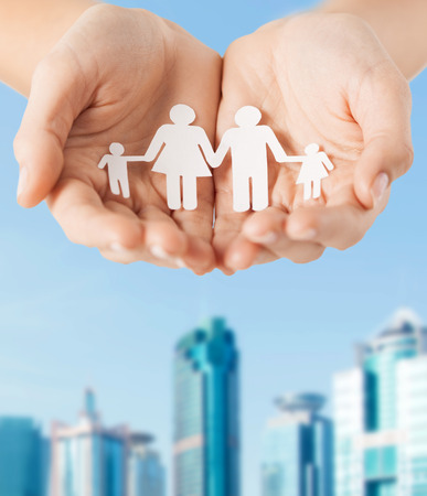 family and relations concept - close up of female cupped hands showing paper man family photo