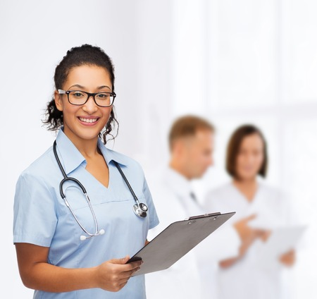 nurse clipboard: healthcare and medicine concept - smiling female african american doctor or nurse in eyeglasses with stethoscope and clipboard Stock Photo