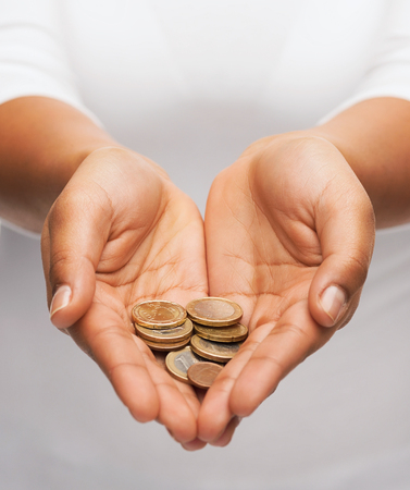 cash money: dinero y las finanzas concepto - cerca de womans manos ahuecadas que muestran las monedas de euro Foto de archivo