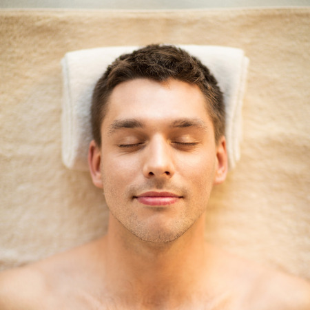 closed eye: healthcare, spa and beauty concept - close up of man face in spa salon Stock Photo