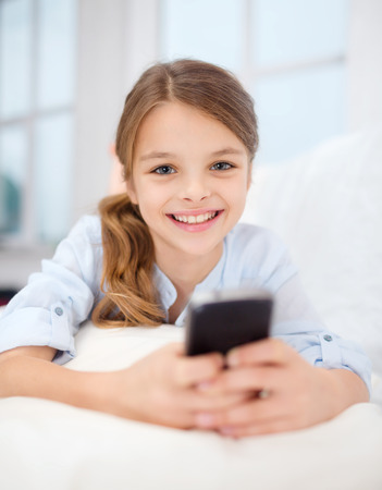 home, leisure, technology and internet concept - little student girl with smartphone at home photo