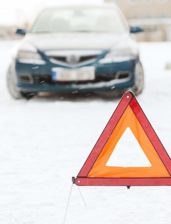 transportation, winter and vehicle concept - closeup of warning triangle and car photo