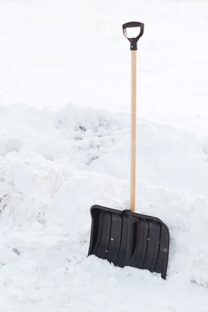 winter and equipment concept - black snowshowel with wooden handle in snow pile photo