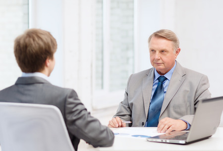 business, technology and office concept - older man and young man having meeting in office photo